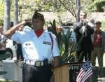Post Commander Dave Loera salutes as Paul Puccinelli performs Taps at Memorial Day service