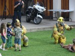 Firefighters in full gear mingle with the kids
