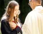 Victoria Haklar receives a blessing from Fr. Richard Krekelberger