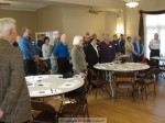Kiwanians, veterans and guests stand to open the meeting