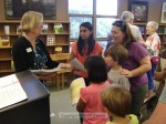 Librarian Meegan Tosh shows children some of the new stuff in the library