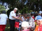 Post Quartermaster Ted Evans passes out poppies and flags